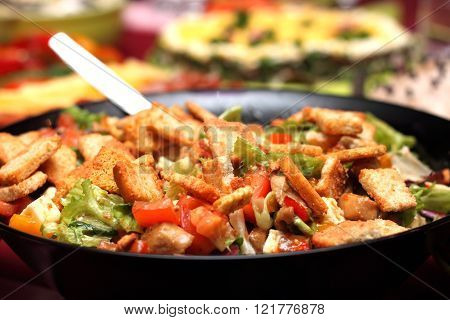 Delicious salad with croutons and vegetables close-up