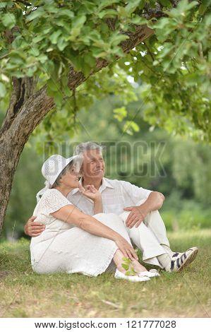 Senior couple sit on a ground
