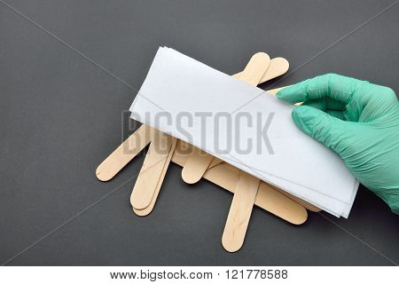 Beauticians Hand With Green Glove Holding Paper Tape For Wax Depilation, Wooden Spatulas For Wax On