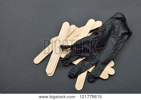 Black Glove And Wooden Spatulas For Wax On Black. Preparing For Epilation