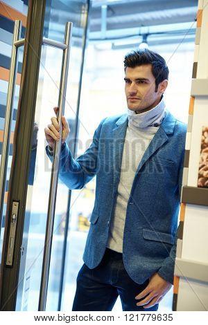 Handsome young man opening door, entering.