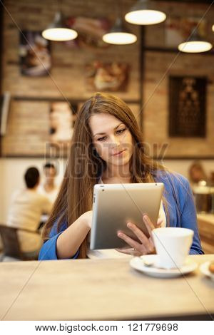 Young woman sitting in cafeteria using tablet computer.