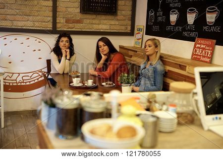 Three bored young single girls sitting in cafeteria, having coffee and cakes.