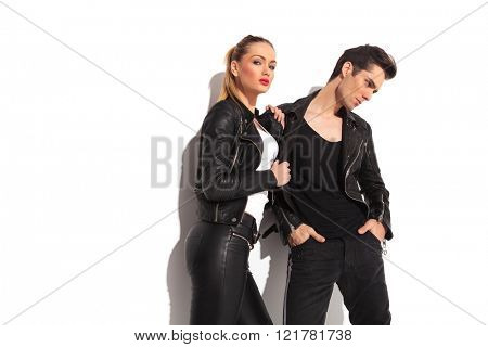 sexy woman pulling her lover by his leather jacket and looks to the camera while he looks away