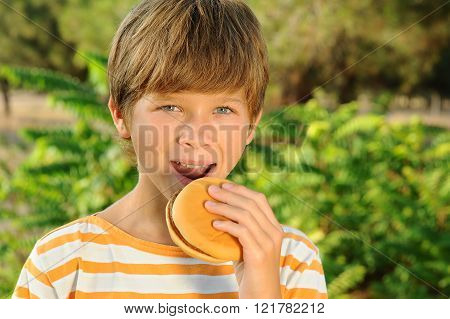 Cute kid boy eating burger outdors. Looking at camera. Teenager biting sandwich over nature background.