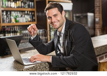Handsome man using laptop computer in a pub