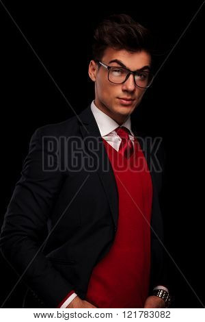 sensual portrait of classy model in black suit wearing glasses posing with hands in pockets while looking at the camera in dark studio background