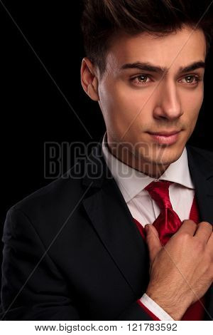 close portrait of young classy male in black suit fixing his tie while looking away from the camera in dark studio background