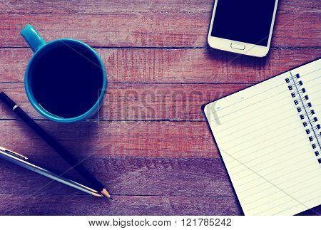 Vintage photo of top view on opened notebook smartphone pen and cup of coffee