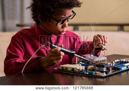 Surprised black boy fixing motherboard.