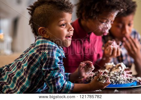 Kids eat cake with hands.