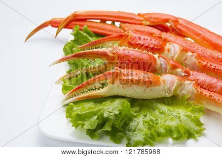 Boiled Crab Claws With Lettuce On A Plate Ovwe White Background
