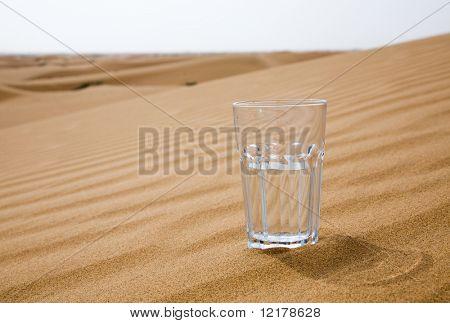 Glass of water half empty on desert