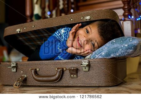 Smiling kid laying inside suitcase.