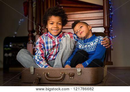Smiling kids sit inside suitcase.