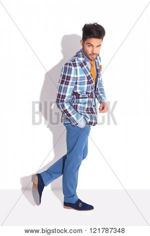 attractive adult walking in studio background with hand in pocket while looking up to the camera
