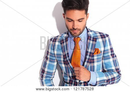 close portrait of casual man in plaid jacket fixing his tie while looking away from the camera in white studio background