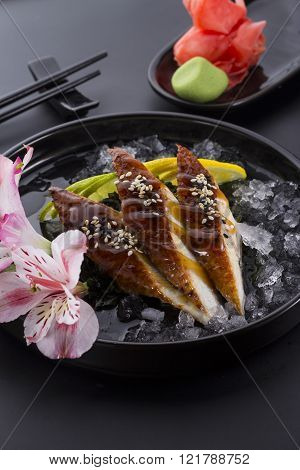 Eel Sashimi With Ice On A Black Plate With Ginger Wasabi Over Black Background