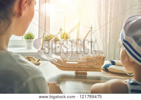 Mother and her child making model ship. Dreams of sea, adventures and travel.