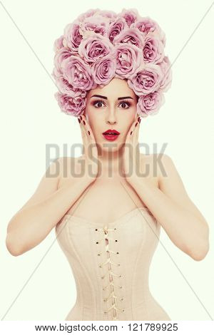 Vintage style portrait of young beautiful slim woman in corset with fancy roses wig on her head and shocked expression