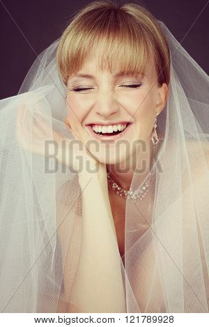Vintage style emotional portrait of young beautiful happy laughing bride in bridal veil