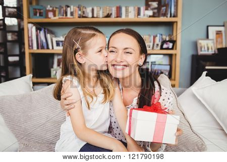 Daughter kissing mother with gift box while sitting on sofa at home