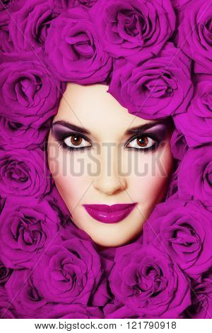 Vintage style close-up portrait of beautiful young girl with smoky eyes and purple roses around her face