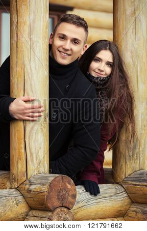 Happy young fashion couple standing on the porch of cottage