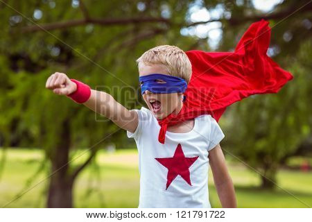 Little boy dressed as superman in the garden