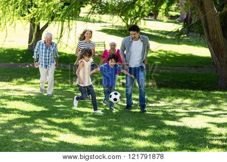 Smiling family playing football in the garden