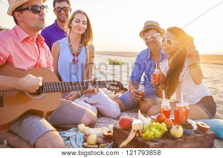 Friends Sitting At The Beach In Circle. One Man Is Playing Guitar
