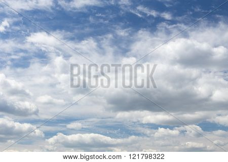 Huge curly white clouds in the blue sky during the day without the sun