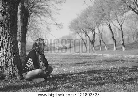 Thoughtful Brunette Sitting Under A Tree In A Park (black-and-white Photo With High Contrast)
