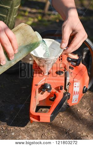 Hand men refilling the chainsaw with fuel