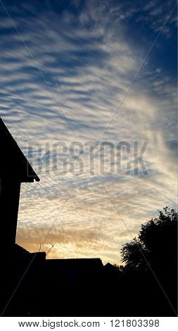 Patterned feathery clouds with sihouettes of houses and trees in the foreground.