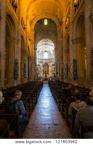 Group Of People Praying Inside The Se Cathedral In Lisbon