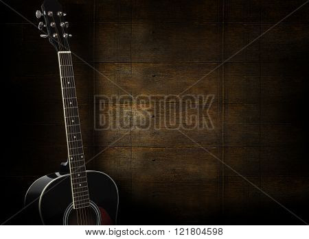 Black Acoustic Guitar On Dark Yellow Wooden Background.