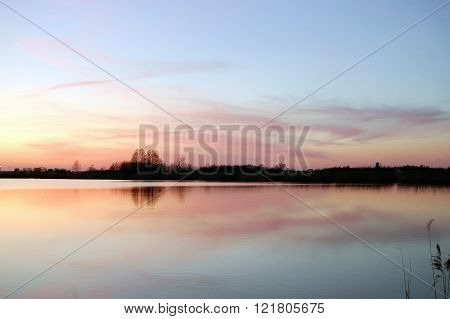 Pink, fuzzy clouds over a lake at sunset