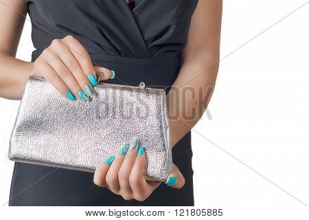 Female Hands With Blue Manicure Opening A Silver Handbag