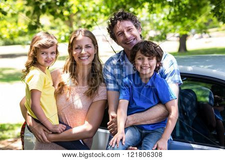Smiling family in front of a car in the park