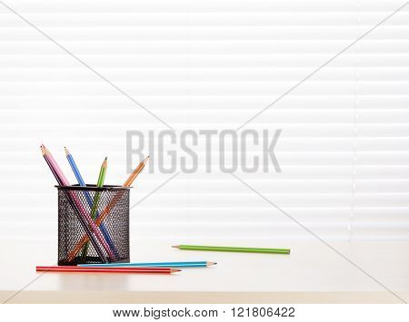 Office workplace with supplies on wood desk table in front of window with blinds