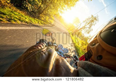 Motorcyclist riding motorbike in sunny morning