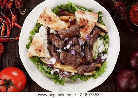 Cevapcici, bosnian minced meat kebab served with french fries, onion and somun bread