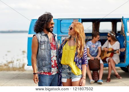 summer holidays, road trip, vacation, travel and people concept - smiling young hippie couple talking over minivan car