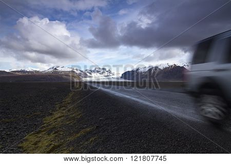 Horizontal photo of an off road car on a straight asphalt road coming from the mountains with clouds above and the Vatnajokull glacier in the background Iceland