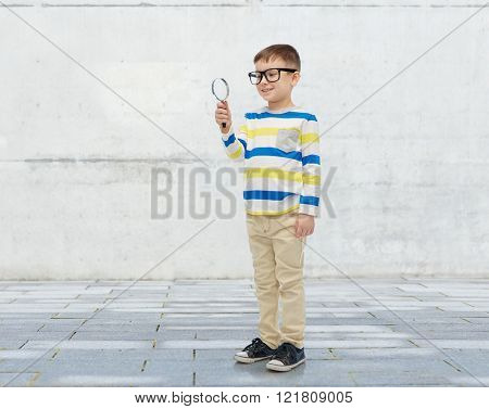 childhood, education, investigation, discovery and people concept - happy little boy in eyeglasses with magnifying glass over urban concrete background