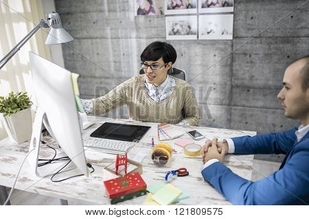 Attractive designer is discussing with her customer