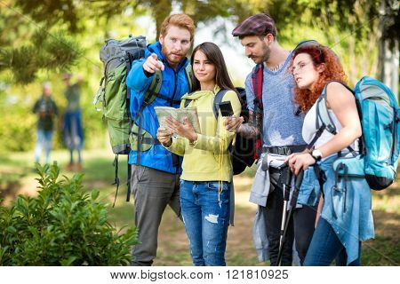 Young mountaineers look at map and at compass for orientation in nature