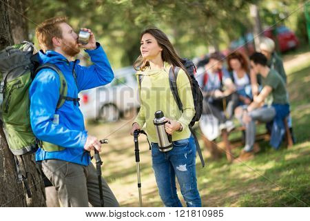 Guy is very thirsty from hiking in forest and drink water offered from his female friend
