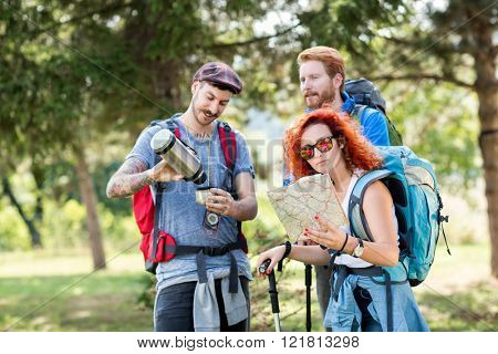 Sports people hiking with backpack, map, thermos and hiking sticks through forest